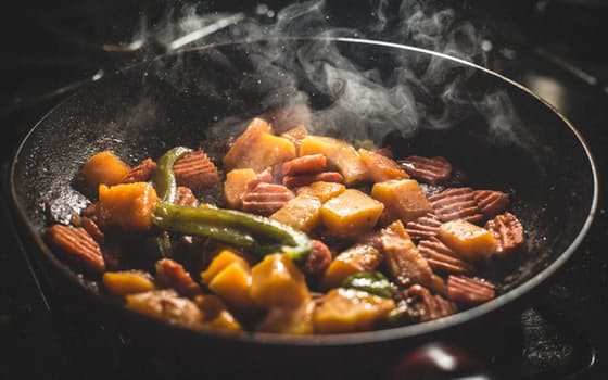 Picture of potatoes, asparagus and meat cooking on a stove.