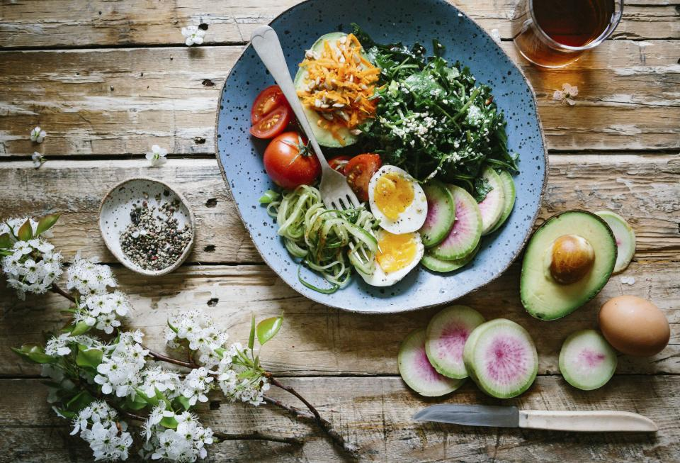 Healthy fruit salad with avocado, eggs, tomatoes, zucchini and spinach