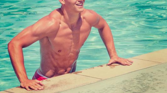 man getting out of the pool with great abs by tim mossholder