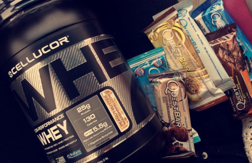Whey protein powdered and five quest protein bars of different flavors.