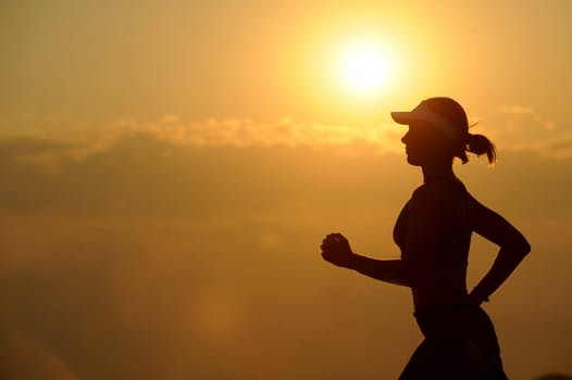 Woman running long distance in the sunset.