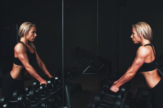 Blonde woman lifting weights at the gym